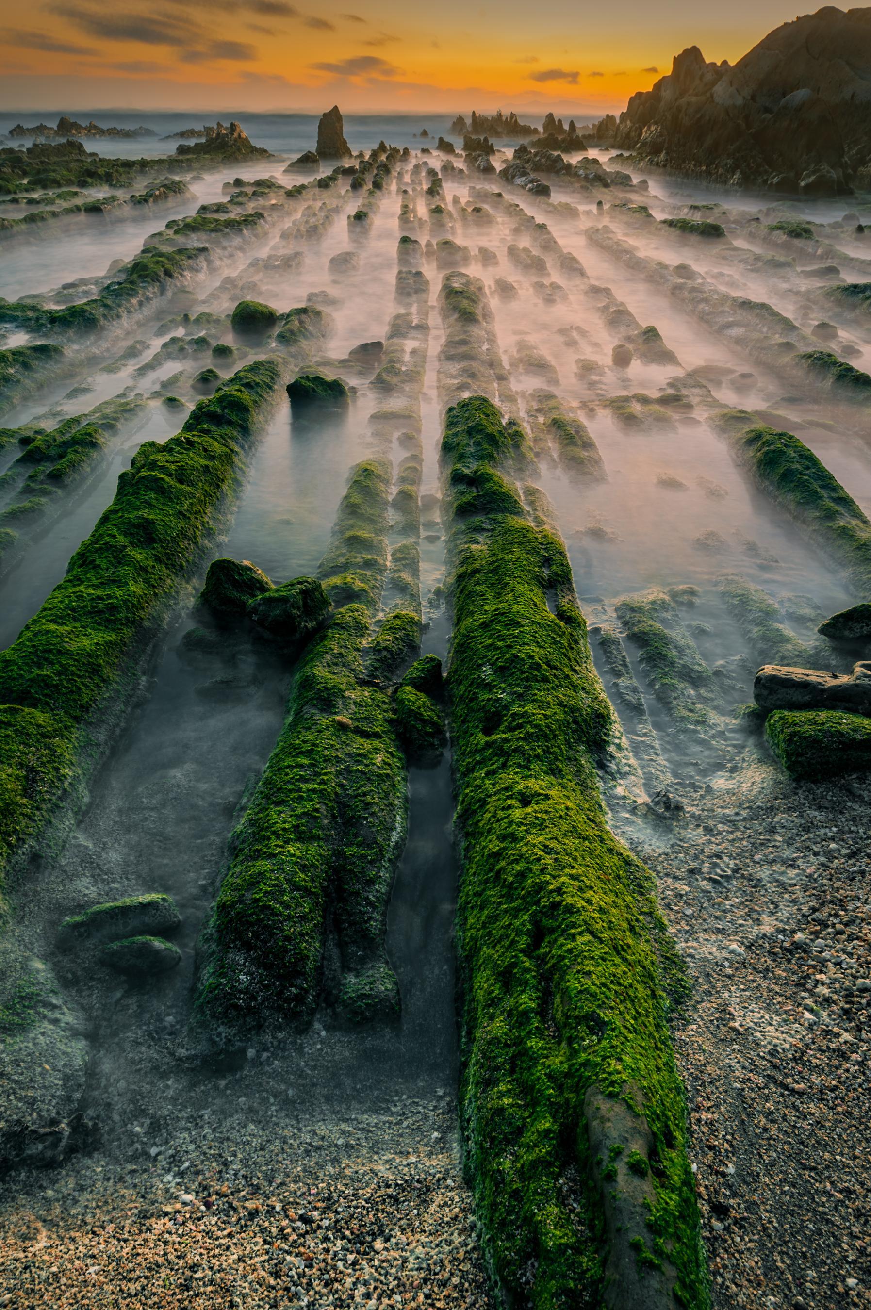 hk_c_一介布衣 位於日本千葉境內,有一處奇特的景觀,每當海水退潮,可以看到無數條青綠的岩石一字排開伸向海的深處,綠色的青苔在夕陽下瀝瀝發光。而漲潮后則又被海水遮掩變得平淡無奇。.jpeg