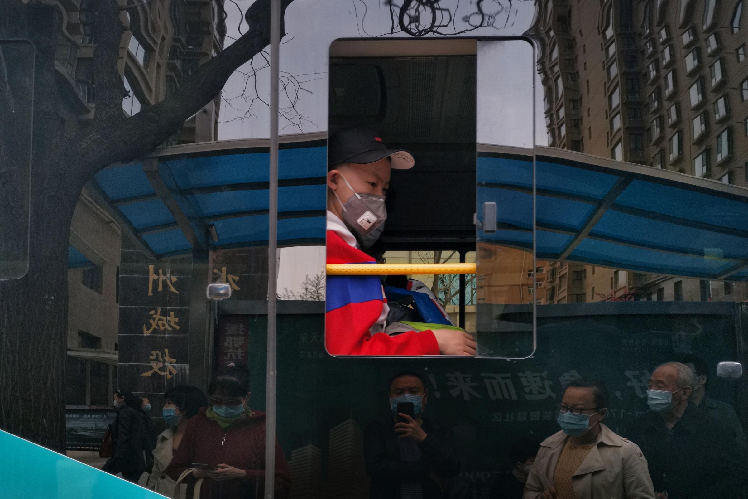 hk_c_6、峰  抓拍疫情下公交車上的孩子和公交車玻璃反光出來的車站等候進站的乘客。.jpeg