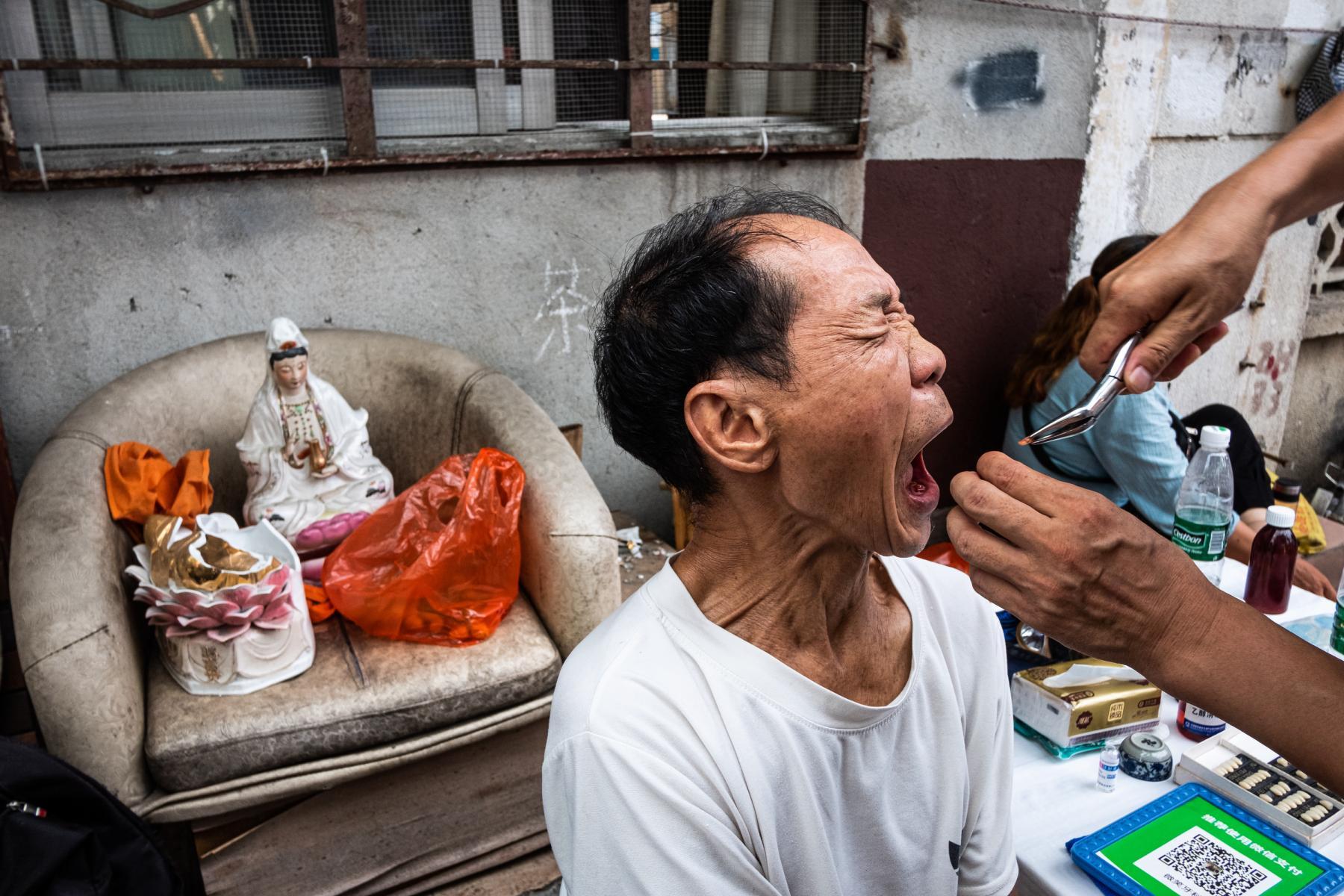 """hk_c_二言大俠  今時今日的現代社會,廣東佛山還能找到街頭拔牙的蹤影。當牙齒被拔出的瞬間,這位大叔的臉上彷彿寫着一個""""痛""""字。.jpg"""